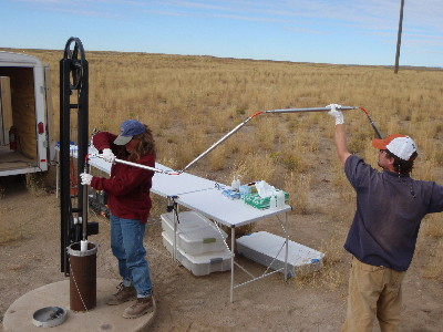 USGS scientists deploying specialized water-sampling bottles into a well equipped with a multilevel monitoring system at the Idaho National Laboratory, Idaho.