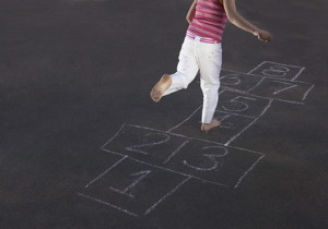 Young girl playing hopscotch on pavement dealed with coal-tar sealcoat.