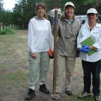 Three scientists holding a sediment core. The core is in a plastic tube