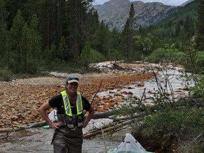 Iron precipitates in a stream - Man standing on gravel bar
