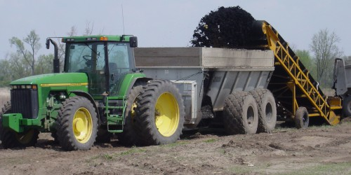 Municipal biosolids being loaded onto spreader for land application