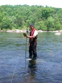 Karl holds a wading rod and discharge measurements.